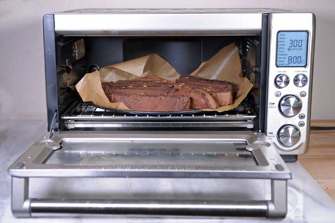 A Breville Smart Oven with a tray of biscotti inside of it. Front view. | Foodal