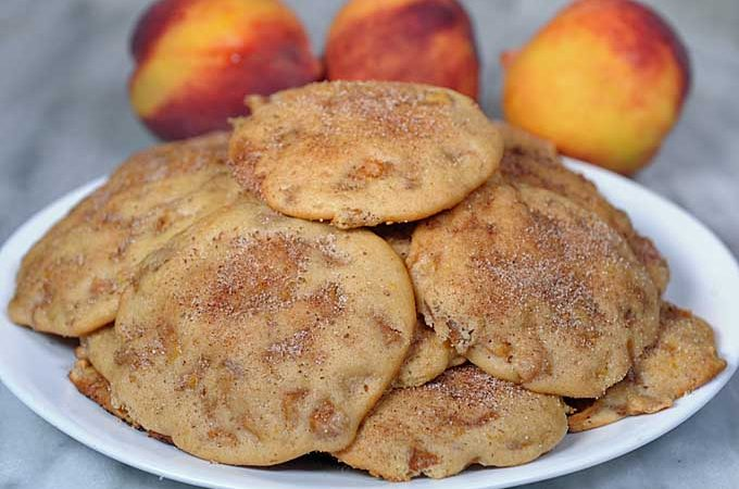 Close up of a plate full of peach cookies. 3 pieces of fresh fruit is in the background | Foodal