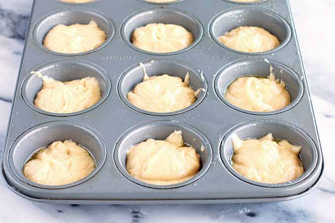 A metal muffin tin with nine wells filled two-thirds of the way with a thick beige batter, on a gray and white marble background.