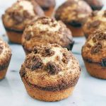 Twelve streusel-topped muffins on a gray and white marble surface.