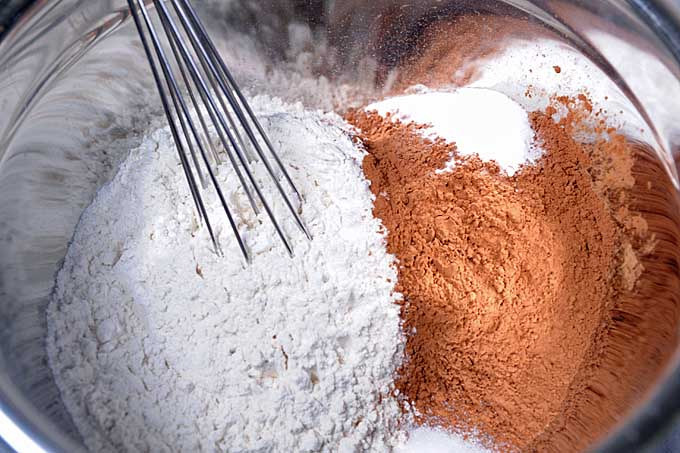 Chocolate powder, baking soda, and flour being whisk together in a small metal mixing bowl | Foodal
