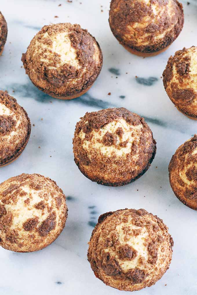 Top-down view of nine muffins topped with cinnamon streusel, on a gray and white marble surface.