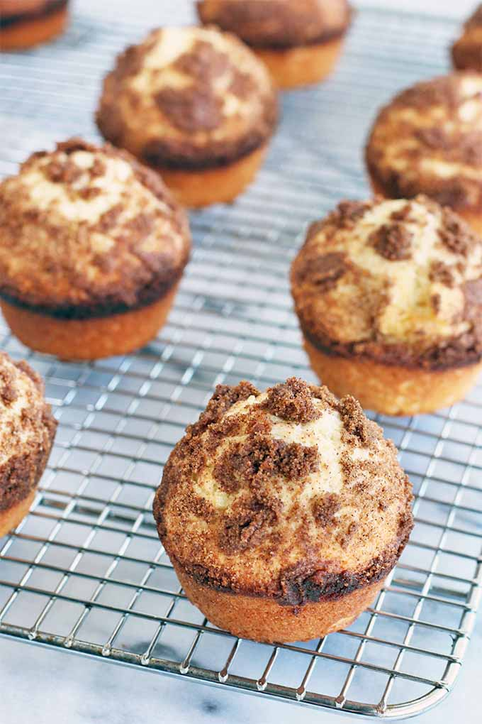 Vertical image shot at an oblique angle of six crumb cake muffins with cinnamon streusel topping, on a wire cooling rack placed on a gray and white marble surface.