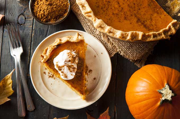 Top view of a slice of pumpkin pie with a whole pie to the upper right and a whole pumpkin at the lower right | Foodal