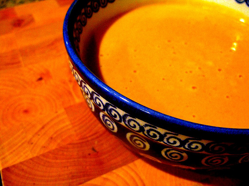 A close up of a bowl of curried pumpkin soup sitting on a wooden table | Foodal