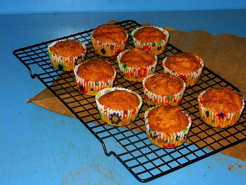 A dozen pumpkin muffins sitting on a cooling rack | Foodal