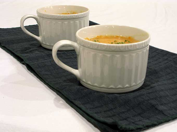 Oblique view of two white ceramic mugs of potato and onion soup | Foodal