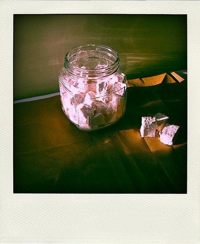 A clear glass cookie jar with homemade pink peppermint marshmallows on a dark background   Foodal
