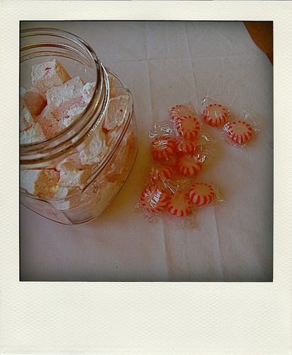 Top view of a glass cookie jar with homemade peppermint marshmallows and crushed peppermint candy next to it   Foodal