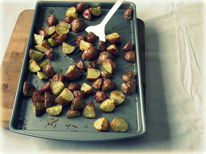 Top view of roasted rosemary red potatoes on a baking pan | Foodal
