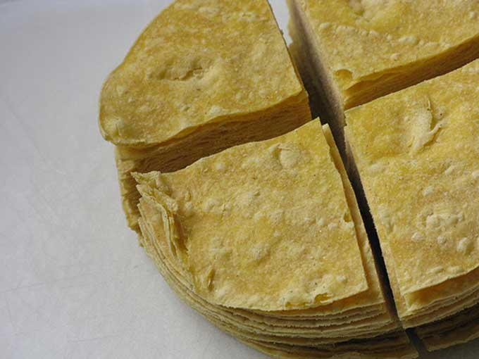 A stack of homemade corn chips made from corn tortillas | Foodal