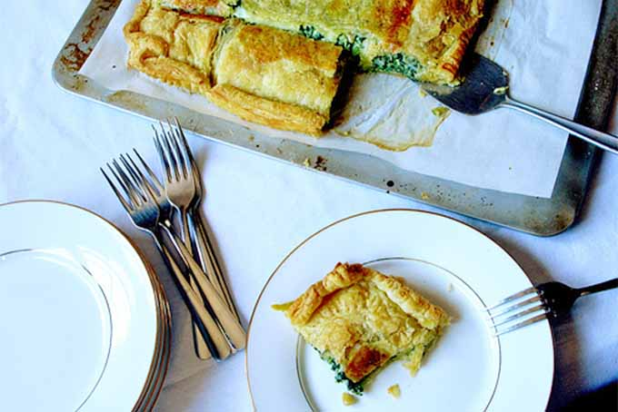 A baking tray topped with a piece of parchment paper and puff pastry filled with spinach, on a white table with two gold-rimmed plates, a stack of forks, and a slice of the pastry on the plate in the foreground.