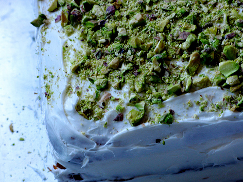 A close up of an old fashioned wedding cake with a crushed pistachio topping | Fooda