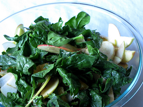 Oblique view of a clear glass mixing bowl with a spinach salad | Foodal