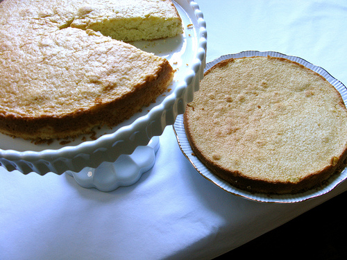 Two seperate layers of a cream cake; one on a cake stand and one on a pie pan | Foodal
