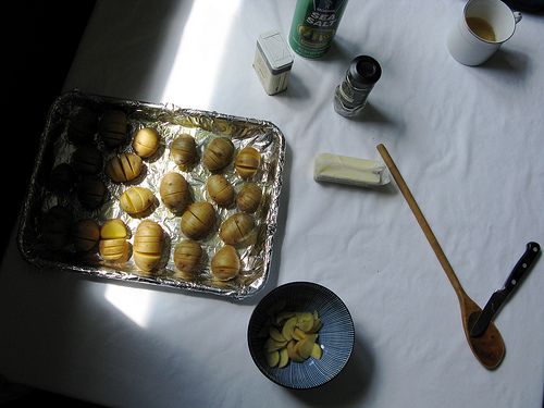 Wide view of raw hasselback potatoes on a baking sheet and other cooking tools used to make the recipe   Foodal