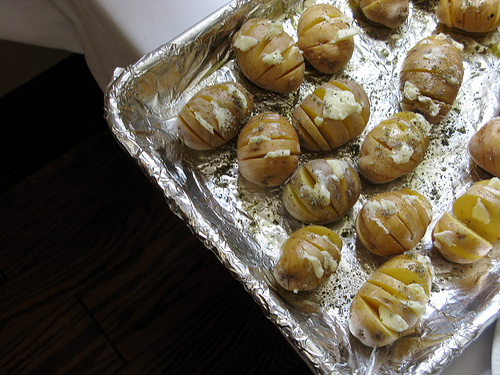 Corner of a backing sheet with potatoes sliced hasselback sty;e with herbed butter   Foodal