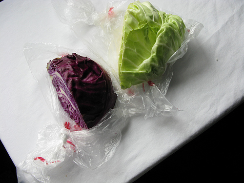 Top down view of two heads of cabbage on a white table cloth   Foodal