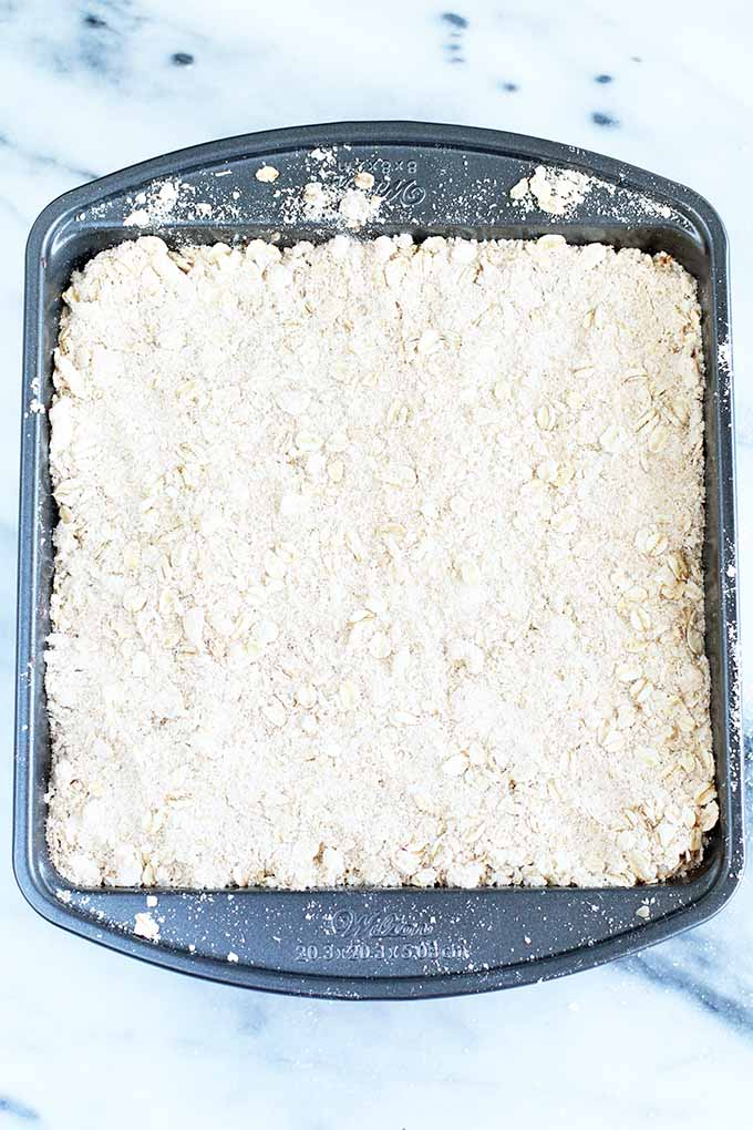 Top-down view of a square metal baking dish of a dessert that is ready to bake, with a flour and oat crumble topping, on a gray and white marble background.