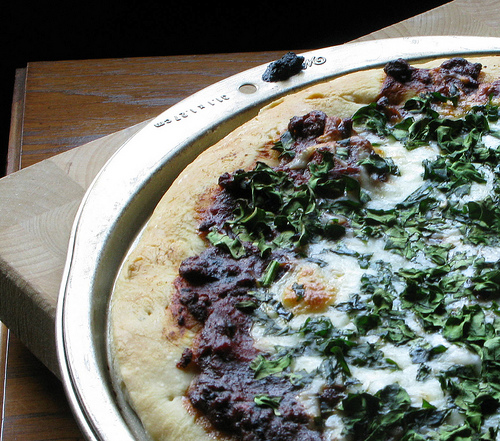 A closeup view of a delicious spinach pizza.