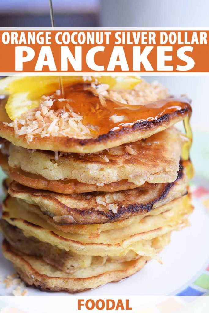 Vertical close-up image of a tall stack of pancakes covered in syrup, coconut flakes, and orange slices, with text on the top and bottom of the image.