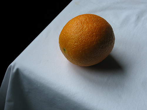 An orange sitting on a white table cloth | Foodal