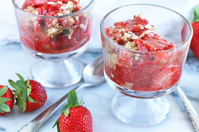 Two parfait glasses of cooked rhubarb and strawberries with a brown sugar and oat crumble topping, with a spoon and three whole strawberries on a marble slab.