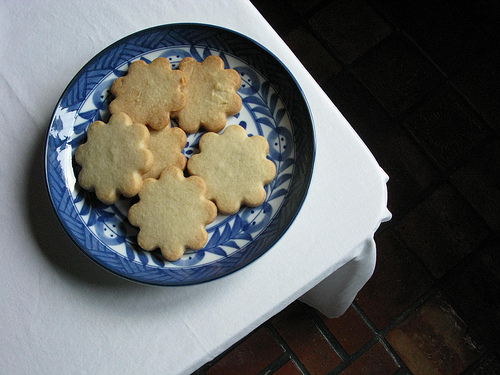 A plateful of plain flower cookies on top of a table covered with white table cloth.