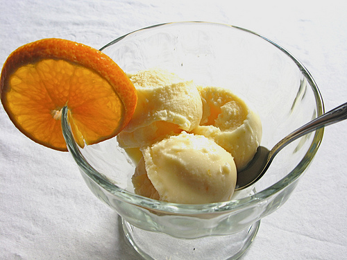 Delicious looking orange sherbet with a garnish of fresh orange slice at the side.