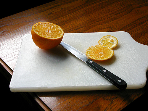 A white chopping board, a knife, and sliced orange on top of a wooden table.