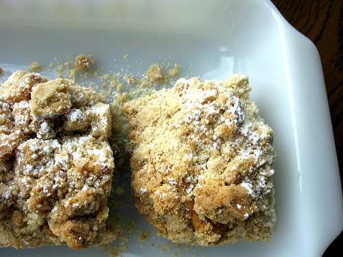 Two slices of delicious rhubarb coffee cake surrounded with big crumbs on a white plate.