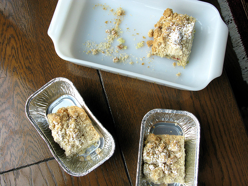 Slices of big-crumb rhubarb cake in various containers on top of a wooden table.
