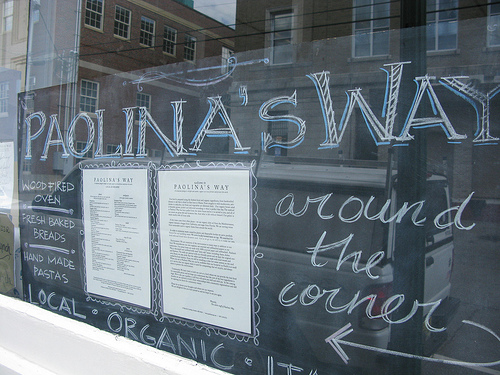 Window decals of a restaurant called Paolina's Way.