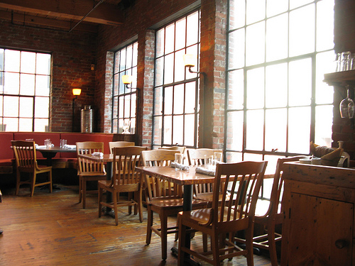 Naturally-lit interior of a restaurant with tables arranged beside tall windows.