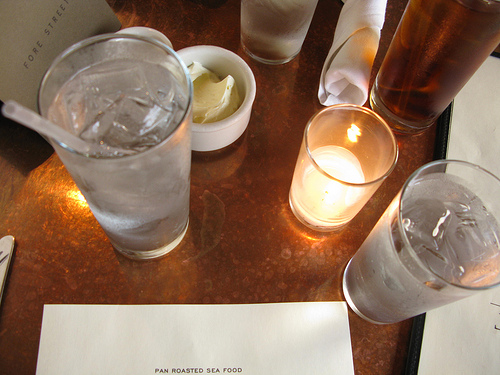 Tall glasses of cold drinks on a candle-lit table.
