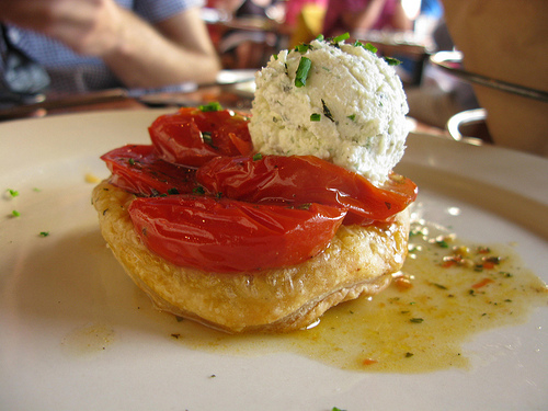 A tomato tart appetizer made with puff pastry and topped with ripe sauteed tomatoes.