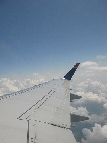 An image of an airplane wingtip, with fluffy clouds and the blue sky as background.