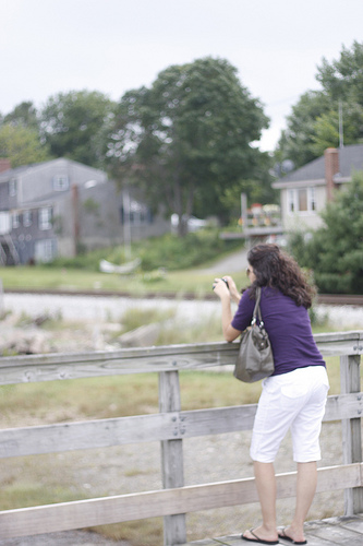 An image of a woman taking a picture of the neighborhood.