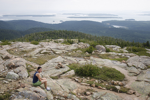 An image of a woman sitting on boulders with a view at the back of distant bay.