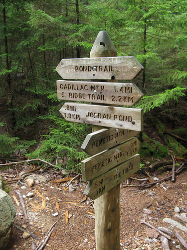A wooden sign on a mountain trail.