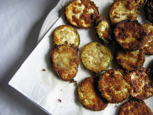 A close up image of a batch of golden brown fried zucchini on top of a napkin.