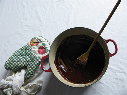 A batter of chocolate mixture in a mixing bowl with a wooden spoon on the side.