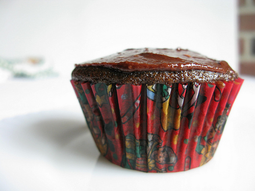 A close up view of a single pomegranate chocolate cupcake with frosting on top.