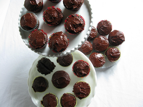 A top view of chocolate cupcakes with frosting, arranged on 3-tier cupcake tray.