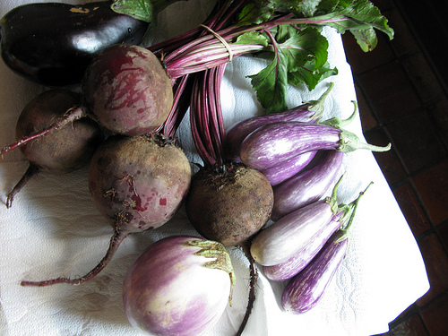 Beets and purple eggplants on a white napkin.