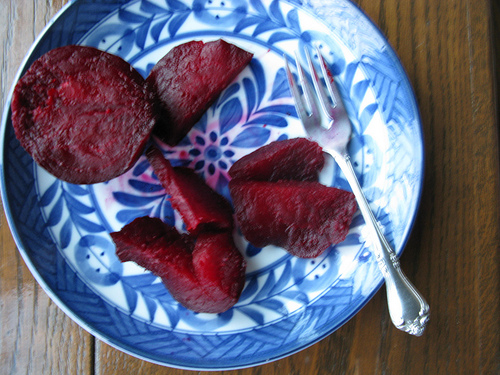 Slices of roasted beets on a white and blue ceramic plate with a fork on the side.