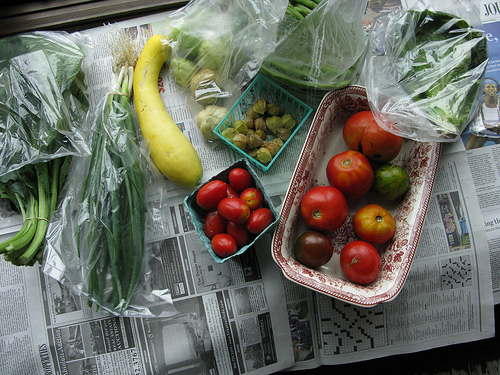 A top view of various vegetables placed on top of an old newspaper.