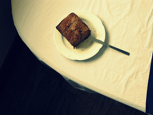 Top view of a slice of banana bread on a white plate with a fork on the side.