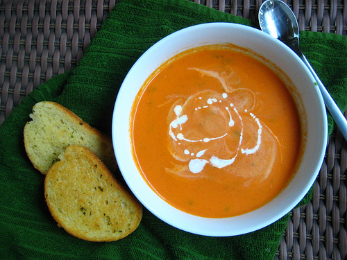 Top view of a bowl of simple but deliciously creamy tomato bisque with two pieces of garlic bread at the side of the bowl.
