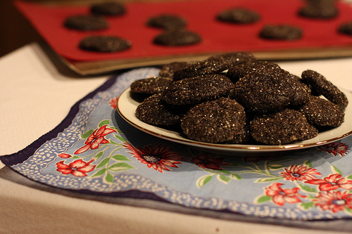 A plate of dark chocolate cookies with more cookies ready for plating at the background.